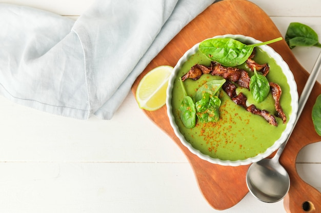Bol avec une savoureuse soupe aux épinards à la lumière