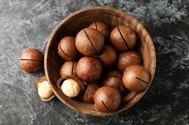 Bol avec de savoureuses noix de macadamia sur mur noir fumé