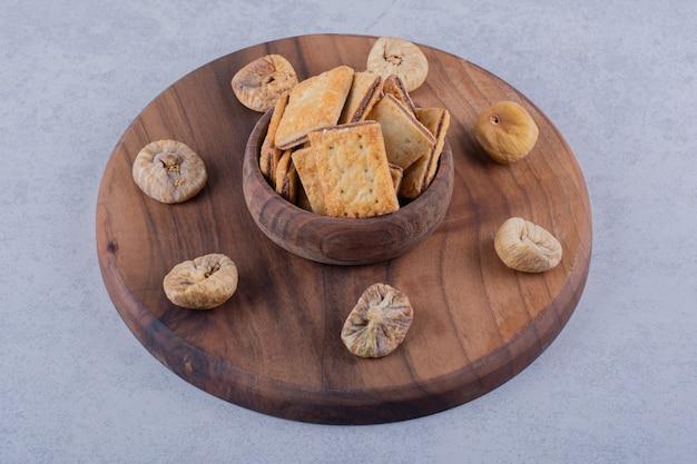 Bol de savoureux craquelins croustillants et figues séchées sur planche de bois.