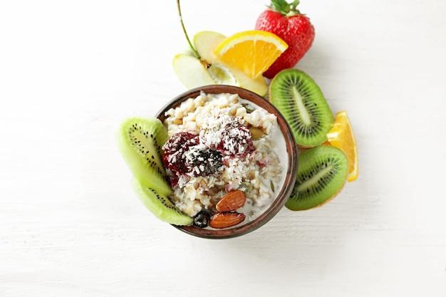 Bol avec savoureux flocons d'avoine, baies et fruits à la lumière