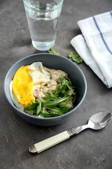 Bol avec de savoureux flocons d'avoine, œuf frit et roquette sur table