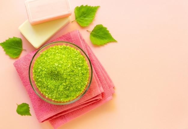 Bol de sel de mer vert et barre de savon sur un fond de couleur