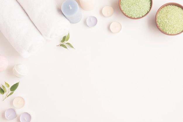 Bol de sel spa vert avec une serviette roulée, des bougies et une bombe de spa sur fond blanc