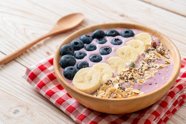 Bol de smoothie au yogourt ou au yaourt avec baies bleues, banane et granola - style alimentaire sain