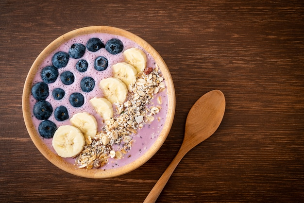 Bol de smoothie au yogourt ou au yaourt avec baies bleues, banane et granola