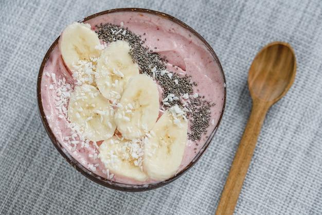 Bol de smoothie aux baies de petit-déjeuner sain garni de graines de banane, de granola et de chia avec espace copie