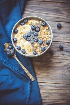 Bol de smoothie aux baies pour petit-déjeuner équilibré avec banane, granola, bleuets et graines de chia