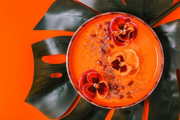 Bol à smoothie avec fleurs de pansy comestibles, graines de chia, baies de goji