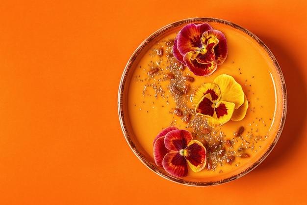 Bol à smoothie avec fleurs de pansy comestibles, graines de chia et baies de goji