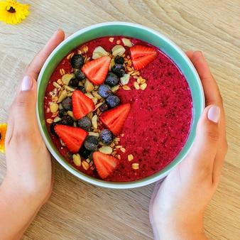 Bol de smoothie frais aux baies d'été avec fraises, baies, granola et amandes