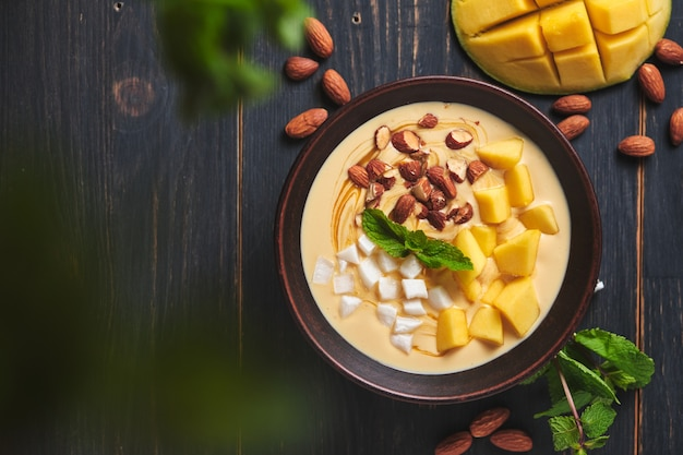 Bol de smoothie tropical avec banane mangue noix de coco et noix