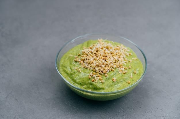 Bol de smoothie vert aux épinards avec des pousses de sarrasin sur fond gris. nourriture végétalienne. concept d'alimentation saine et de nutrition