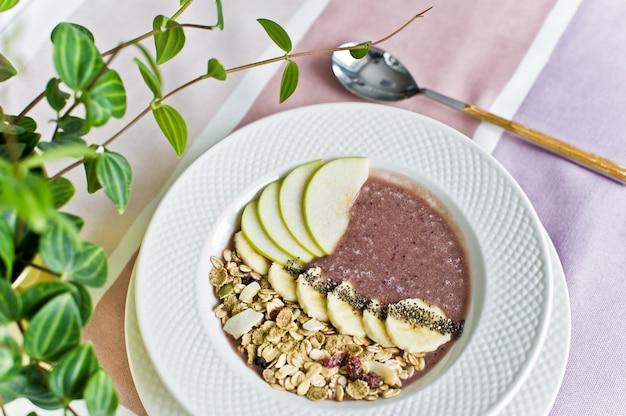 Bol à smoothies avec banane, pomme, graines de chia, céréales et yaourt.