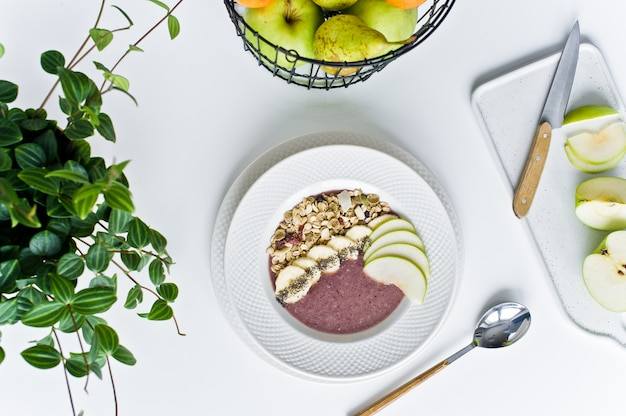 Bol à smoothies avec banane, pomme, graines de chia, flocons d'avoine et yaourt.