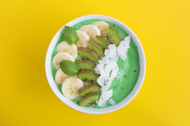 Bol de smoothies avec chips de banane, kiwi et noix de coco au centre de la surface jaune.