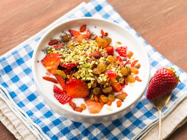 Bol à smoothies avec fraises, fruits secs et graines de chia