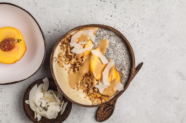 Bol à smoothies avec pouding au chia, pêche, noix de coco et granola dans un bol à la noix de coco.