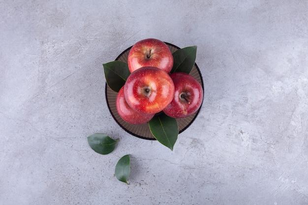 Bol sombre avec des pommes rouges brillantes sur pierre.