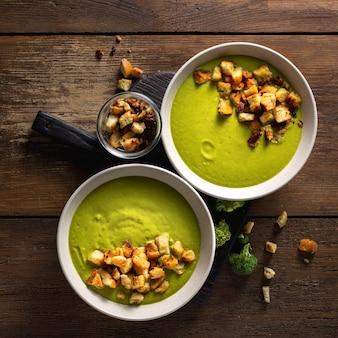 Bol de soupe au brocoli à la crème avec des croûtons de pain sur une table en bois