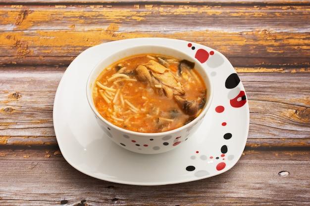 Bol avec soupe au poulet sur table en bois