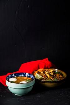 Bol de soupe aux légumes et aux boulettes de poisson avec des nouilles et une serviette de table rouge sur fond noir