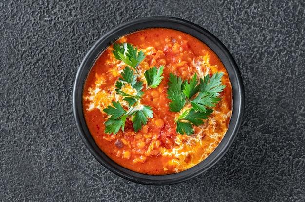 Bol de soupe aux lentilles, tomates et noix de coco à plat