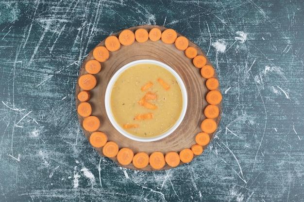 Bol de soupe aux lentilles et tranches de carottes sur plaque en bois.