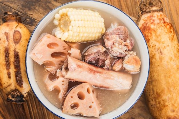 Bol de soupe aux racines de lotus os de porc sur une table en bois