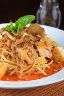 Bol de soupe blanc avec des spaghettis et des morceaux de pain décorés de légumes verts