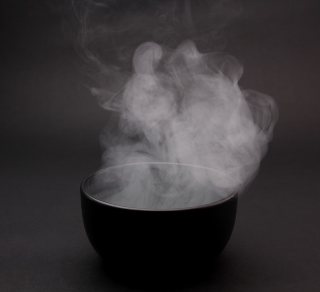 Bol de soupe chaude sur fond noir
