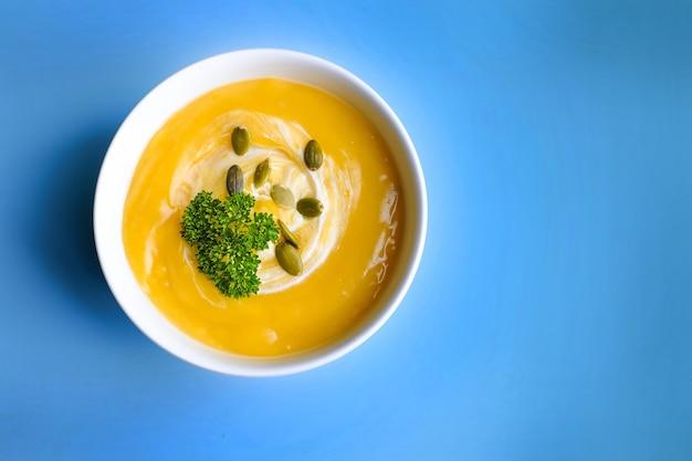 Bol de soupe à la citrouille avec feuille verte. vue de dessus