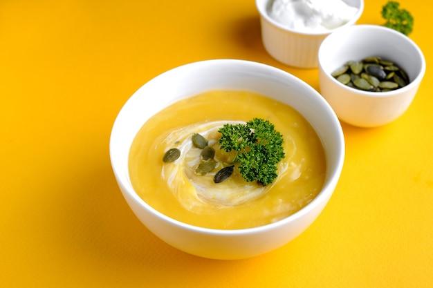Bol de soupe à la citrouille avec feuille verte