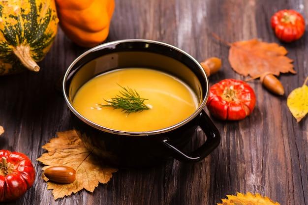Bol de soupe à la citrouille sur une table en bois