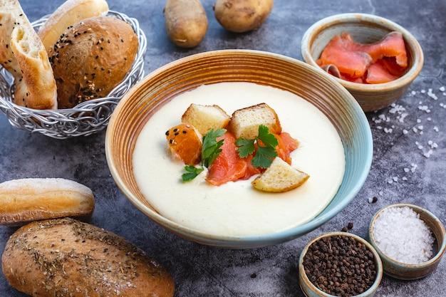 Bol de soupe crémeux garni de farce de pain de saumon et de persil