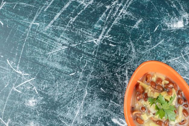 Bol de soupe délicieuse avec des pâtes et des haricots sur l'espace bleu.