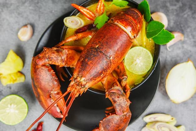 Bol de soupe épicée au homard rouge - fruits de mer cuits avec table de dîner au homard et ingrédients d'épices sur la plaque noire de la nourriture thaïlandaise, tom yum kung