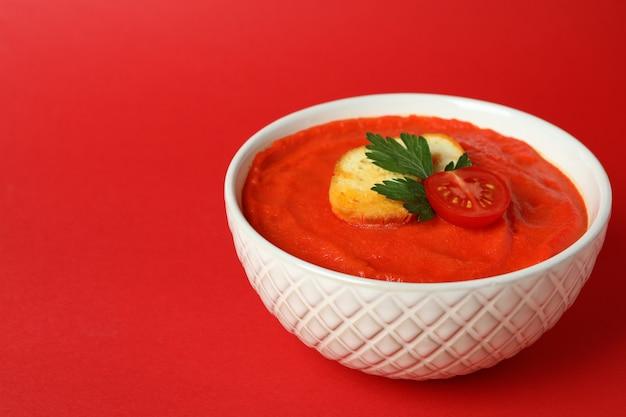 Bol de soupe gaspacho savoureuse sur fond rouge