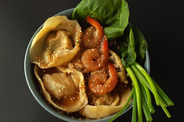 Bol de soupe de nouilles aux crevettes, wontons et épinards
