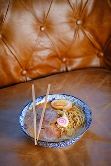 Bol de soupe de nouilles savoureuse avec de la viande et des œufs sur un fauteuil en cuir