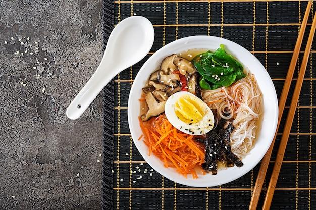 Bol de soupe de nouilles végétarienne aux champignons shiitake, carottes et œufs durs. nourriture japonaise. vue de dessus. pose à plat