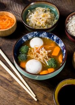 Bol de soupe de poisson et de poisson, servi avec pousses de haricots et carotte râpée sur une table en bois