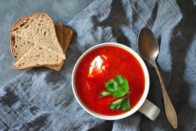 Bol de soupe de racine de betterave rouge bortsch avec crème blanche sur fond rustique gris. regarder.