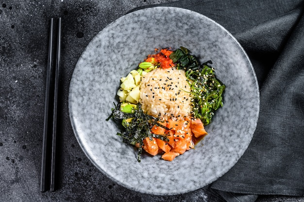 Bol à sushi avec concombre, saumon, avocat. cuisine asiatique à la mode. fond noir. vue de dessus. copiez l'espace.