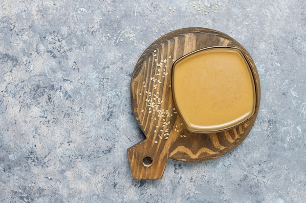 Bol de tahini aux graines de sésame sur une surface en béton