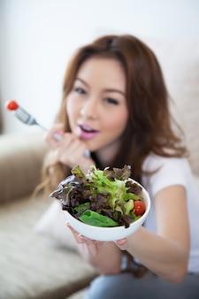 Bol de tenue de salade par les femmes asiatiques