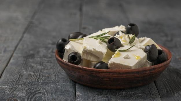 Un bol en terre cuite avec des tranches de fromage feta, des olives et de l'huile d'olive sur une table en bois. fromage naturel au lait de brebis.
