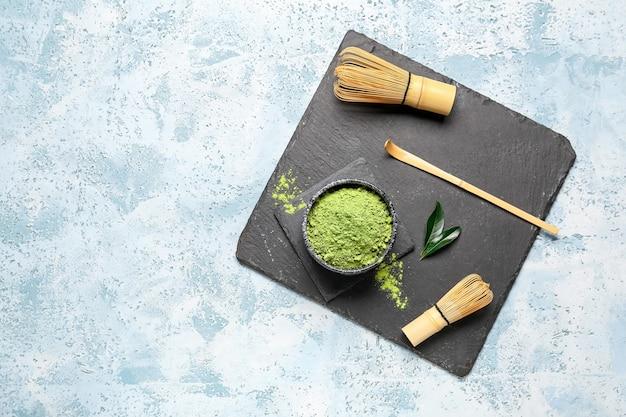 Bol avec thé matcha en poudre, chashaku et chasen sur fond de couleur
