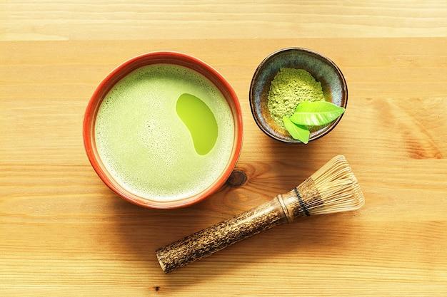 Un bol de thé matcha sur une table en bois avec un fouet et de la poudre.