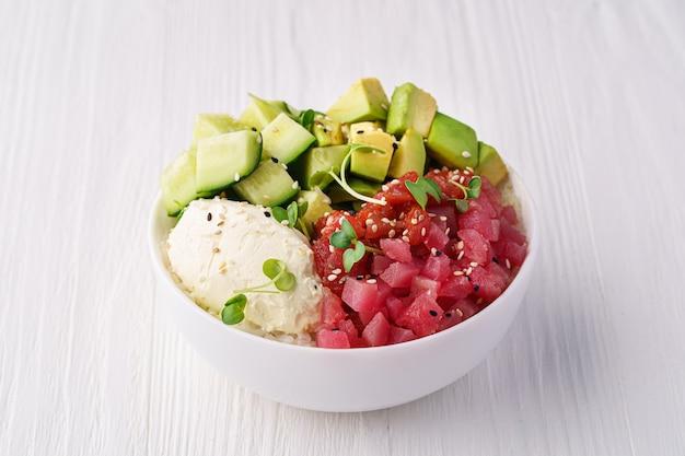 Bol avec thon, riz, fromage à la crème d'avocat, concombre et pousses de pois et graines de sésame sur une table en bois blanc
