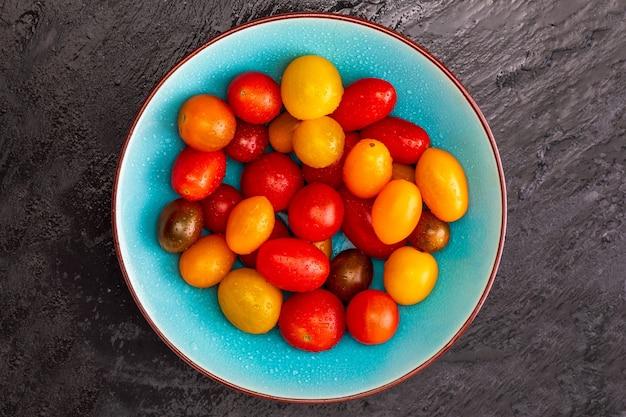 Bol de tomates cerises colorées (rouge, grenat et jaune), fraîches et crues. avec des gouttes d'eau. sur fond texturé noir et espace pour insérer du texte (espace de copie). vue de dessus